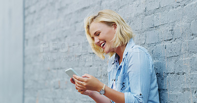 Buy stock photo Shot of a confident young woman texting on a cellphone outdoors