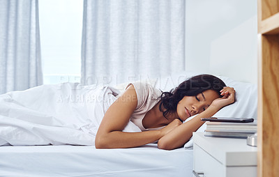 Buy stock photo Shot of a young woman sleeping peacefully in her bed at home