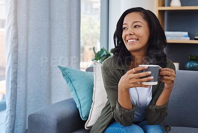 Buy stock photo Shot of an attractive young woman having coffee and relaxing on the sofa at home