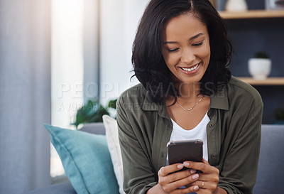 Buy stock photo Shot of an attractive young woman using a smartphone on the sofa at home