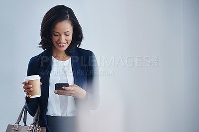 Buy stock photo Shot of a young businesswoman using a cellphone in an office