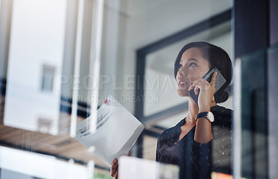 Buy stock photo Shot of a young businesswoman talking on a cellphone while going through paperwork in an office