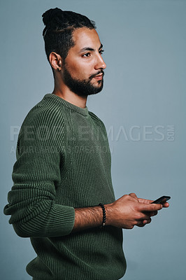 Buy stock photo Studio shot of a handsome and stylish young man using a smartphone against a grey background
