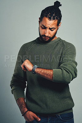 Buy stock photo Studio shot of a handsome and stylish young man checking the time on his watch against a grey background