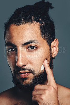 Buy stock photo Studio portrait of a handsome young man applying moisturiser to his face against a grey background