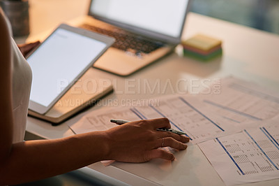 Buy stock photo Shot of an unrecognizable businesswoman using her digital tablet and laptop while working late in her office