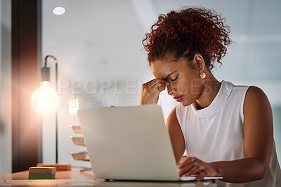 Buy stock photo Shot of a young businesswoman suffering from a headache while working late in her office