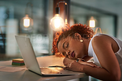 Buy stock photo Shot of an exhausted young businesswoman sleeping at her desk during a late night at work