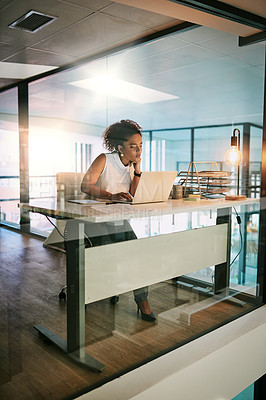 Buy stock photo Full length shot of a young businesswoman working on her laptop during a late night in the office