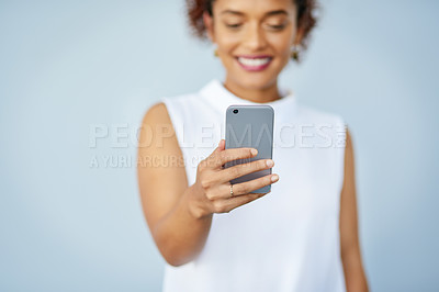 Buy stock photo Studio shot of a confident young businesswoman holding her cellphone against a gray background