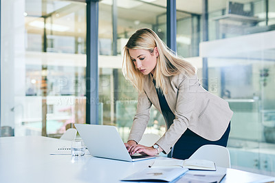 Buy stock photo Cropped shot of an attractive young businesswoman working on a laptop in her corporate office