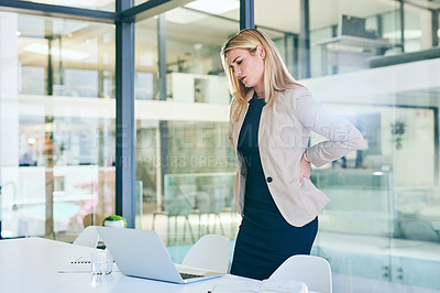 Buy stock photo Cropped shot of an attractive young businesswoman suffering with backache while working in her corporate office
