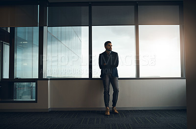 Buy stock photo Shot of a young businessman leaning against a wall and looking thoughtful in a modern office