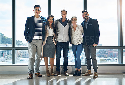 Buy stock photo Portrait of a group of confident young businesspeople standing together in the office at work during the day