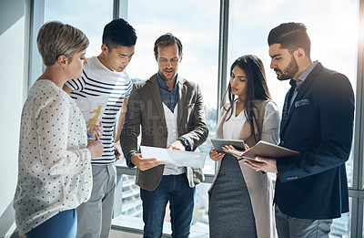 Buy stock photo Cropped shot of a group of young businesspeople having a discussion together inside of the office during the day
