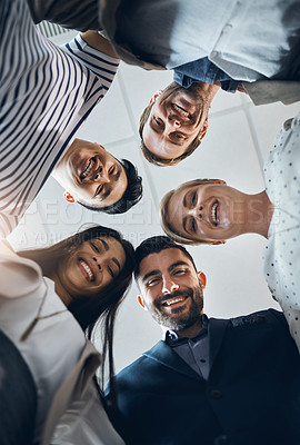 Buy stock photo Low angle portrait of a group of confident young businesspeople standing together in the office at work during the day