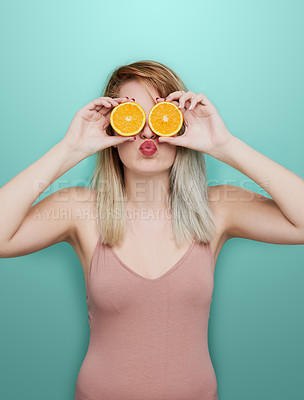 Buy stock photo Studio shot of an attractive young woman holding two pieces of fruit in front of her eyes while standing against a colored background