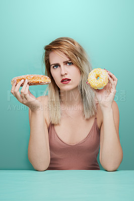 Buy stock photo Studio shot of an attractive young woman posing with consumables against a colored background