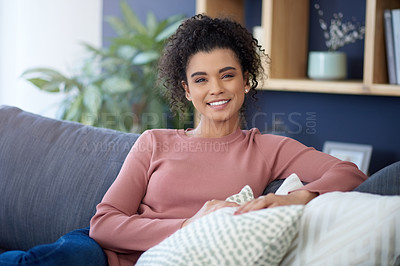 Buy stock photo Cropped portrait of an attractive young woman relaxing on her sofa at home