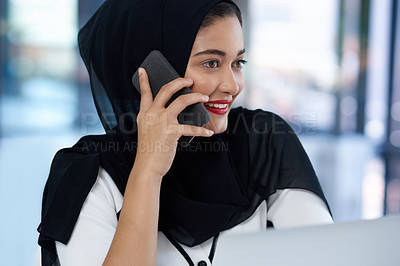 Buy stock photo Shot of a young businesswoman using a laptop and smartphone in a modern office