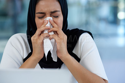 Buy stock photo Shot of a young businesswoman blowing her nose at her desk in a modern office