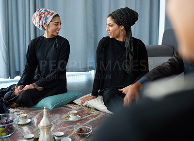 Buy stock photo Shot of two beautiful young muslim women having a conversation at a gathering with friends indoors