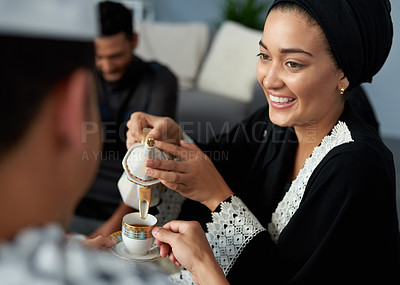 Buy stock photo Shot of a young muslim woman pouring tea for her friend during a gathering indoors