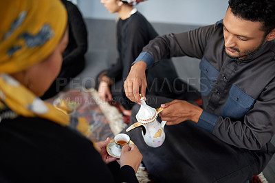 Buy stock photo Shot of a handsome young muslim man pouring tea for a friend at a gathering indoors