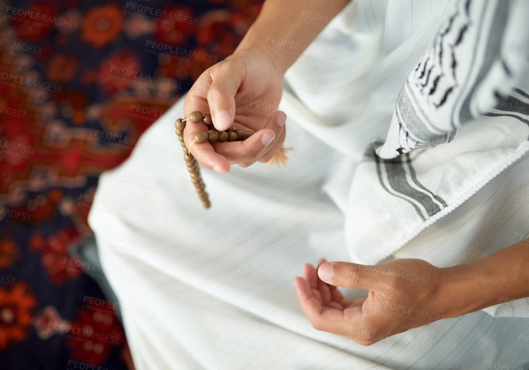 Buy stock photo Shot of an unrecognizable muslim man sitting down and holding prayer beads in his hand indoors