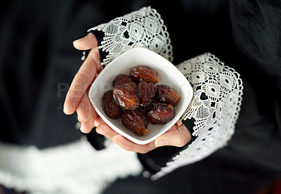 Buy stock photo Shot of an urecognizable muslim woman sitting down and holding a bowl of treats indoors