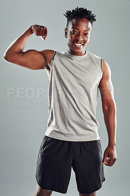 Buy stock photo Shot of a sporty young man flexing against a grey background