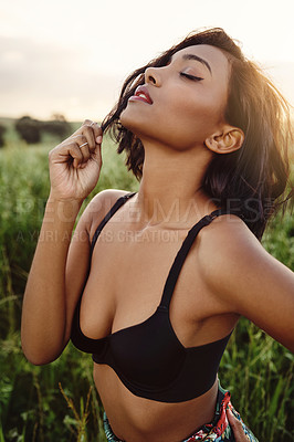 Buy stock photo Cropped shot of a beautiful young woman posing in her bra outdoors