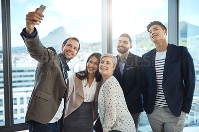 Buy stock photo Shot of a group of businesspeople taking a selfie together in an office