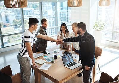 Buy stock photo Shot of a diverse group of businesspeople joining their hands in a huddle in an office