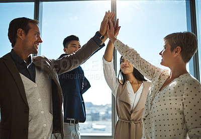 Buy stock photo Shot of a diverse group of businesspeople giving each other a high five in an office
