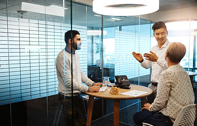 Buy stock photo Cropped shot of three young businesspeople having a meeting in their office