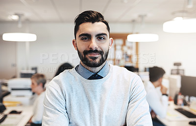Buy stock photo Cropped portrait of a handsome young businessman in the office while his colleagues are working in the background