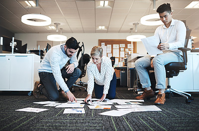 Buy stock photo Full length shot of three young businesspeople working on paperwork together on the floor in the office