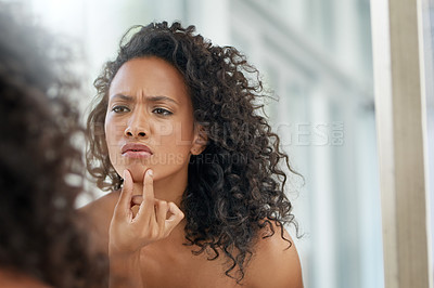 Buy stock photo Shot of an attractive young woman inspecting her face in the bathroom mirror