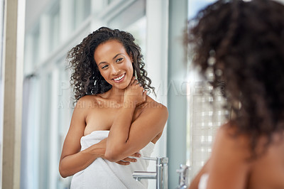 Buy stock photo Shot of an attractive young woman admiring her face in the bathroom mirror