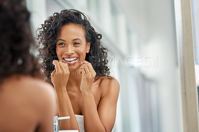 Buy stock photo Shot of an attractive young woman flossing her teeth in the bathroom at home