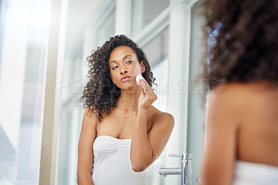 Buy stock photo Shot of an attractive young woman wiping her face with a cotton pad during her morning beauty routine