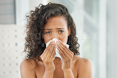 Buy stock photo Shot of a young woman blowing her nose with a tissue during her morning routine at home