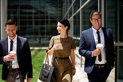 Buy stock photo Shot of three cheerful  businesspeople walking together outside an office building