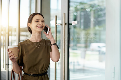 Buy stock photo Shot of a beautiful young businesswoman making a phone call while walking outside an office building
