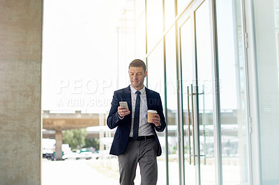 Buy stock photo Shot of a handsome businessman using his cellphone while walking outside an office building