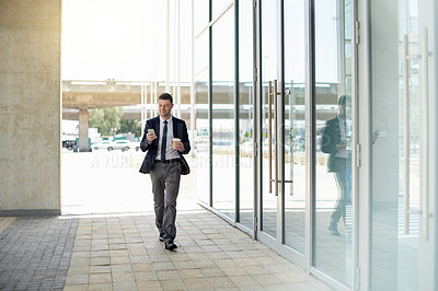 Buy stock photo Full length shot of a handsome businessman using his cellphone while walking outside an office building