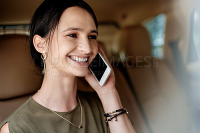 Buy stock photo Shot of a beautiful young businesswoman taking a phone call while sitting in the backseat of a car