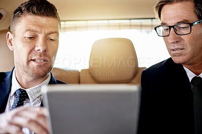 Buy stock photo Shot of two mature businessmen using a digital tablet together while sitting in the backseat of a car