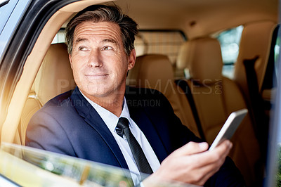 Buy stock photo Shot of a handsome businessman using a cellphone while sitting in the backseat of a car